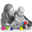 kid boy and mother playing together with cup toys